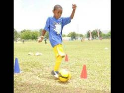 With deep concentration etched on his face, this young Ballaz participant practises kicking the football.