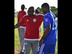 Paul Davis whispers instructions to Ricardo Gaynor before the 15-year old make his Red Stripe Premier League debut against Molynes United last Sunday at the Constant Spring Football Field.