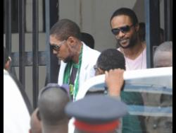 Entertainers Vybz Kartel (left) and Shawn Storm leave the Home Circuit Court, where they were sentenced to life imprisonment in 2014.