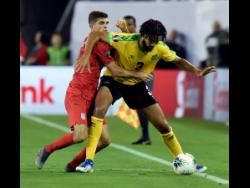 United States midfielder Christian Pulisic and Jamaica defender Michael Hector (right) battle for the ball during the second half of their Concacaf Gold Cup semi-final match in Nashville, Tennessee, on Wednesday, July 3, 2019.