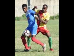 Portmore United's Shai Smith (left) shields the ball from Humble Lion's Levaughn Williams during their Red Stripe Premier League match at the Spanish Town Prison Oval on Sunday.