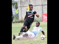 Cavalier's Chevone Marsh (on feet) evades a sliding tackle by Portmore United's Emelio Russeauduring a Red Stripe Premier League match on Sunday, February 10, 2019.