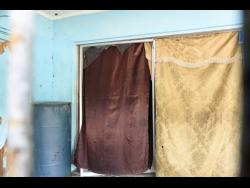 Makeshift curtains are used to cover glass doors of a St Andrew house where residents say gay sex workers operate a brothel.