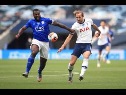 Leicester's Wes Morgan (left) and Tottenham's Harry Kane vie for the ball during their English Premier League match at the Tottenham Hotspur Stadium in London, England, on Sunday.