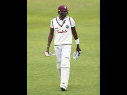 West Indies captain Jason Holder walks off the field after being dismissed by England's Chris Woakes during the fifth day of the third Test match against England at Old Trafford in Manchester, England, on Tuesday.