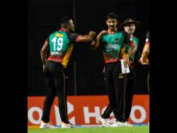 Sheldon Cottrell (left), Ish Sodhi (centre)  and Ben Dunk of St Kitts & Nevis Patriots celebrate the dismissal of Jason Holder of Barbados Tridents during the Hero Caribbean Premier League match two between Barbados Tridents and St Kitts & Nevis Patriots at the Brian Lara Cricket Academy in  Trinidad and Tobago yesterday.