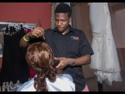 Ricardo Downer applies make-up to a client.