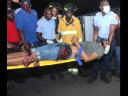 Kemar Archer is carried by fire and medical personnel to the ambulance.