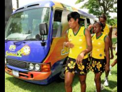 File Sunshine Girls Kasey Evering (left), Sateva Taylor (centre) and Romelda Aiken walk next to one of the    netball team buses shortly after it was presented to the Jamaica Netball Association by Jamaica Public Service Company Limited in August 2010.