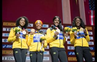 Members of Jamaica's female sprint relay team pose with their gold  medals after winning the event at the World Athletics Championships in Doha, Qatar. From left: Natalliah Whyte, Shelly-Ann Fraser-Pryce, Jonielle Smith and Shericka Jackson.