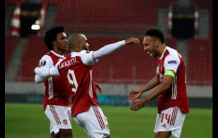 Arsenal's Pierre-Emerick Aubameyang right, celebrates with teammates after scoring his sides third goal during the Europa League round of 32, second leg, match between Arsenal and Benfica at Georgios Karaiskakis stadium, in Piraeus port, near Athens, yesterday.