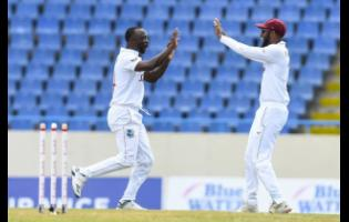 West Indies' bowler Kemar Roach reacts with captain Kraigg Brathwaite (right) after one of the three wickets he claimed to help reduce Sri Lanka to 169 all out on Day One of the first Test in Antigua on Sunday, March 21.