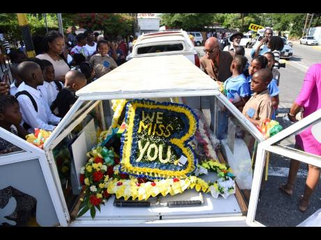 Children gather around the chariot holding Benjamin's body, as the hearse prepares to head for Dovecot Memorial Park.