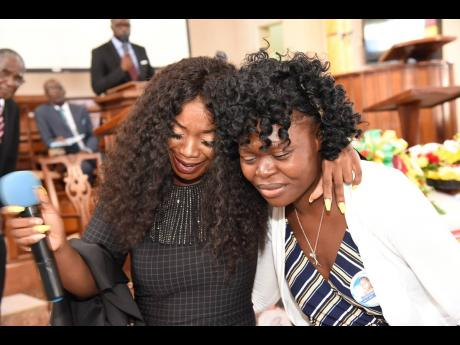 Pamputtae (left) tries to comfort Japhene Campbell, mother of Benjamin Bair, at the youngster's funeral yesterday at the North Street Seventh-day Adventist Church.