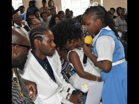 Courtney Greaves (right), a schoolmate of Benjamin's, offers a rosebud to members of his family during the funeral.