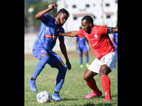 Dunbeholden's Deandre Thomas (left) taking on  UWI FC's  Fabion McCarthy  during their  Red Stripe Premier League encounter at the UWI Bowl on Sunday, January 12.