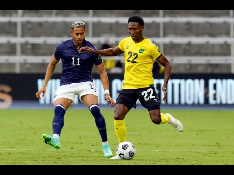 Jamaica's midfielder Devon Williams (right) moves the ball past Costa Rica forward Ariel Lassiter (11) during the first half of last night's Concacaf Gold Cup Group C  match in Orlando, Florida.