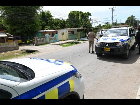 Police outside the crime scene in Gregory Park, St Catherine.